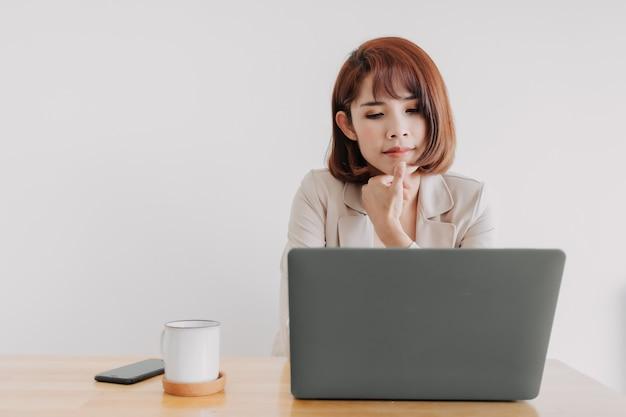 La femme qui travaille utilise un ordinateur portable sur le bureau avec un fond blanc