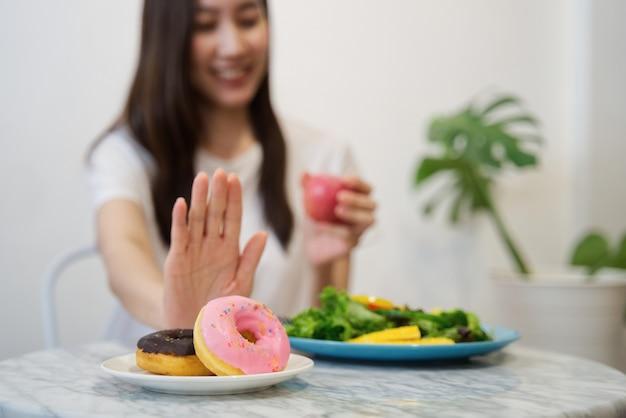 Une femme qui utilise ses mains rejette la malbouffe en poussant ses beignets préférés et choisit une pomme rouge.