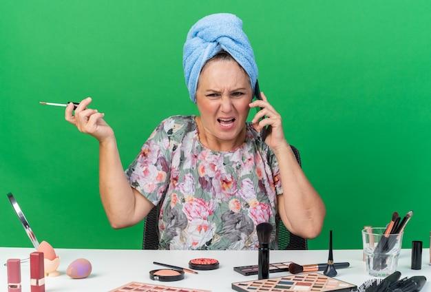 Femme de race blanche adulte agacée avec des cheveux enveloppés dans une serviette assis à table avec des outils de maquillage criant à quelqu'un tenant un brillant à lèvres