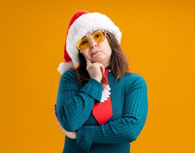 Femme de race blanche adulte réfléchie dans des lunettes de soleil avec bonnet de noel et cravate de père noël met le doigt sur le visage et regarde la caméra isolée sur fond orange avec espace de copie