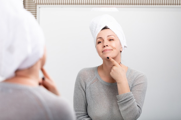 Femme de race blanche d'âge moyen avec une serviette de bain sur la tête