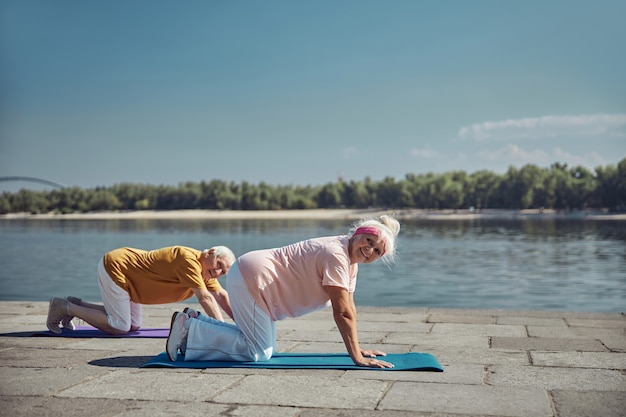 Femme de race blanche âgée pleine d'entrain et un homme posant pour la caméra pendant l'entraînement de yoga