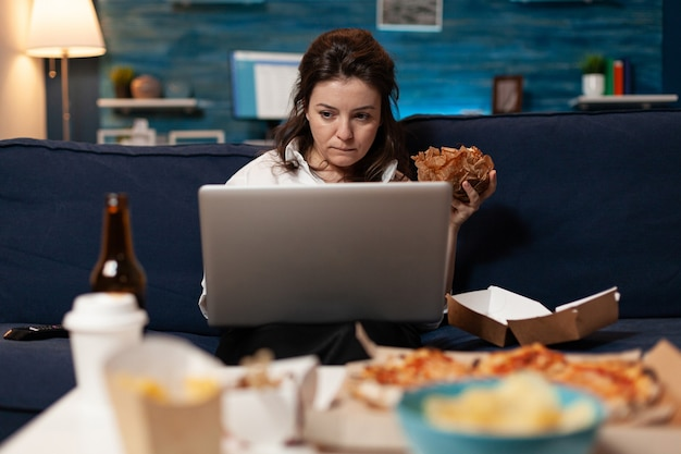 Femme de race blanche assise sur un canapé en train de manger un délicieux hamburger délicieux tout en travaillant sur un ordinateur portable