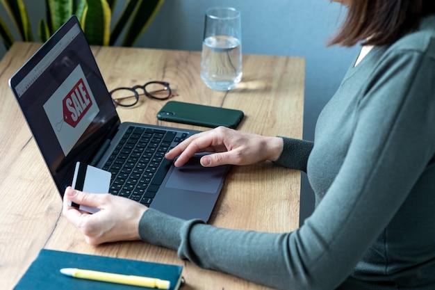 Une femme de race blanche au bureau à domicile travaille et paie en ligne, en surfant sur internet et en faisant des achats en ligne. payer par carte bancaire, moyens de paiement modernes, paiements électroniques paiements en ligne