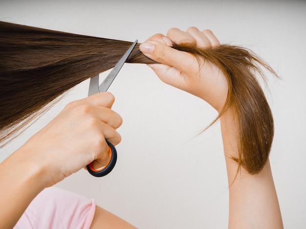 Femme de race blanche aux cheveux longs essayant de se faire couper les cheveux avec des ciseaux en quarantaine pendant la pandémie de covid-19.