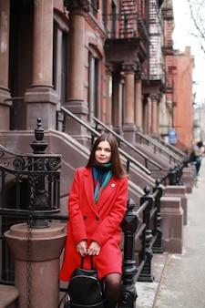 Une femme de race blanche aux cheveux noirs et vêtue d'un manteau rouge se tient à l'extérieur de la ville sur une pop clairsemée
