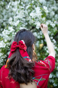 Femme de race blanche avec de beaux cheveux ondulés et un clip d'arc devant un arbre en fleurs au printemps
