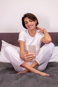 Femme de race blanche blogueuse à la maison dans des vêtements décontractés chambre confortable prendre selfie photo sur téléphone mobile dans le miroir