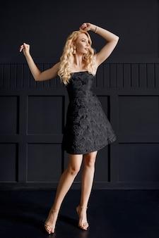 Femme de race blanche blonde en petite robe noire sur la fête sur fond noir