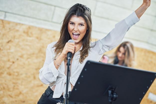 Femme de race blanche chantant dans un microphone en studio