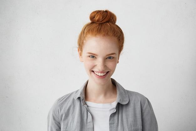 Femme de race blanche avec chignon de cheveux roux à la recherche de ses yeux charmants bleus démontrant son sourire sincère. jolie femme rousse naturelle étant heureuse