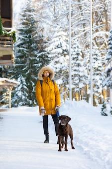 Femme de race blanche dans une veste jaune avec un chien debout dans la nature des bois d'hiver à pied avec un chien