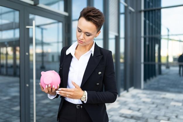 Femme de race blanche dans des vêtements de bureau est titulaire d'une tirelire cochon rose et attend un collègue près de l'immeuble de bureaux
