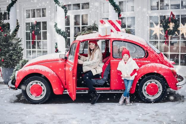 Femme de race blanche dans la voiture avec sa fille et beaucoup de neige à l'extérieur