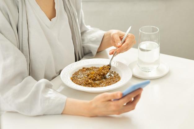 Une femme de race blanche déjeune avec son téléphone dans les mains et est distraite par les médias sociaux