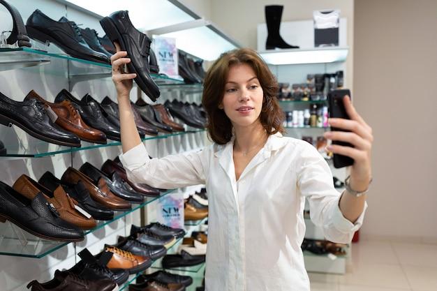 Femme de race blanche faire selfie avec des chaussures d'homme noir dans un magasin de chaussures