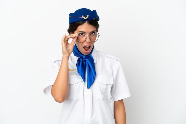 Femme de race blanche hôtesse d'avion isolé sur fond blanc avec des lunettes et surpris
