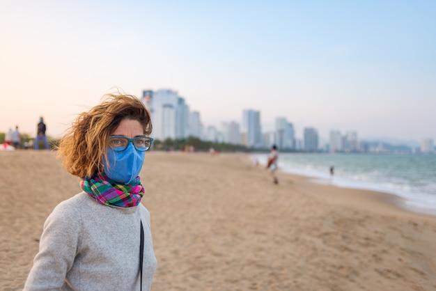 Femme de race blanche portant un masque sanitaire à l'extérieur sur la plage de nha trang, célèbre destination voyage au vietnam. touriste avec masque médical protection contre le risque de nouveau virus corona covid-19 en asie