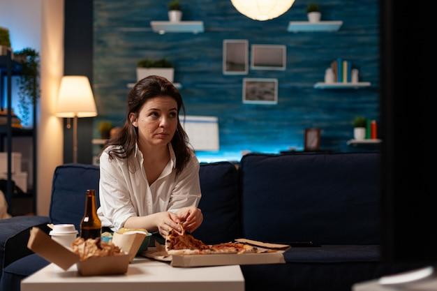 Femme de race blanche prenant une délicieuse tranche de pizza mangeant une commande de restauration rapide à domicile