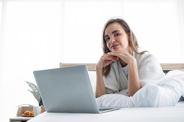 Femme de race blanche en pyjama jouant social dans un ordinateur portable sur un lit blanc.