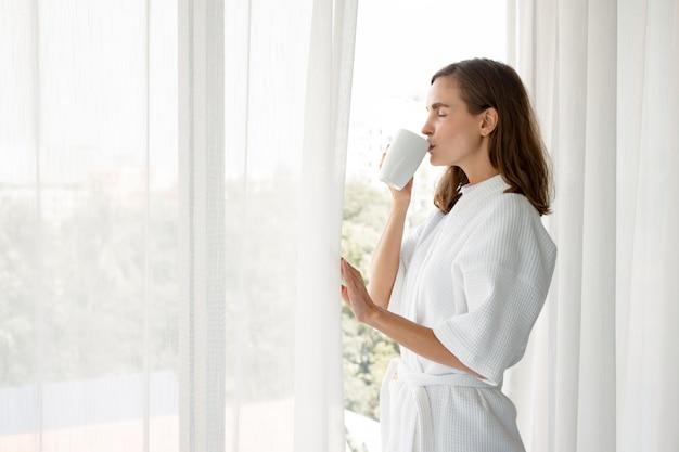 Femme de race blanche en pyjama tenant un verre de café blanc prêt à boire par la fenêtre.