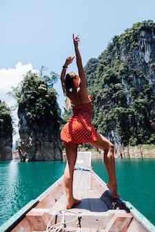 Femme de race blanche en robe d'été rouge sur un bateau asiatique thaïlandais en vacances, voyager en thaïlande