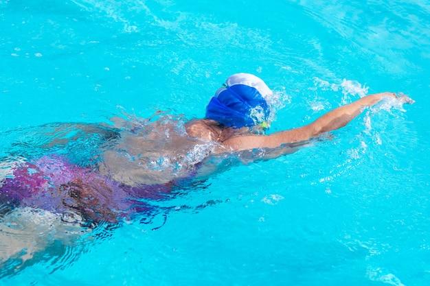 Femme de race blanche senior en activité nageant en nage libre dans la piscine extérieure