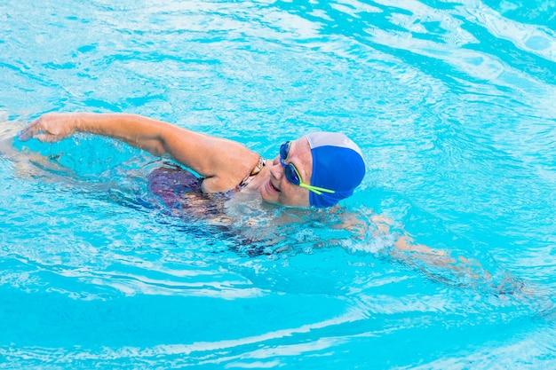 Femme de race blanche senior en activité natation en nage libre pratiquer le sport dans la piscine