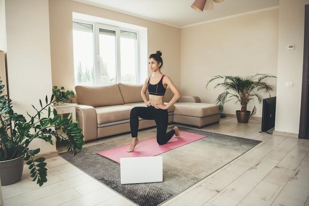 Femme de race blanche sportive ayant des cours de fitness en ligne à l'aide d'un ordinateur portable et portant des vêtements de sport sur le sol à la maison