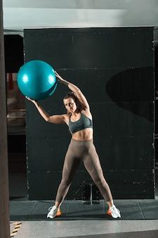 Femme de race blanche sportive vêtue de vêtements de sport et avec queue de cheval soulevant la balle de pilates en se tenant debout dans la salle de gym.