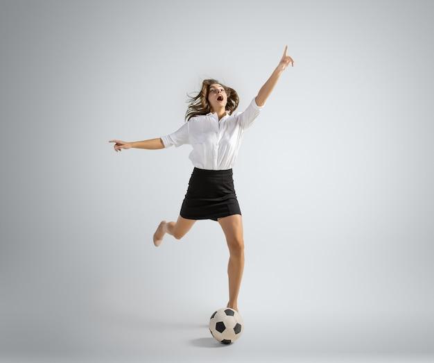 Femme de race blanche en vêtements de bureau donnant un coup de pied au ballon isolé sur un mur gris