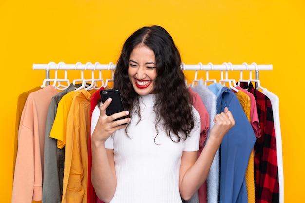 Femme de race mixte dans un magasin de vêtements et de parler au mobile