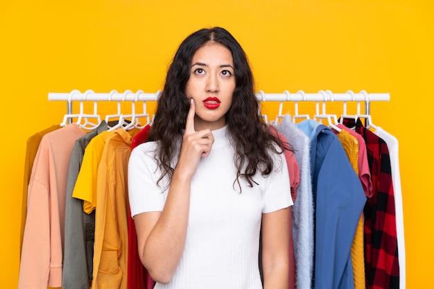 Femme de race mixte dans un magasin de vêtements en pensant à une idée