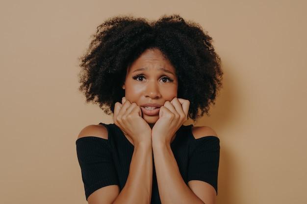 Femme de race mixte effrayée regardant nerveusement et ressentant du stress tout en posant sur fond beige