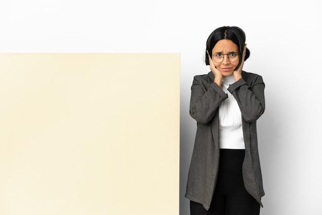 Femme de race mixte jeune entreprise avec une grande bannière sur fond isolé frustré et couvrant les oreilles