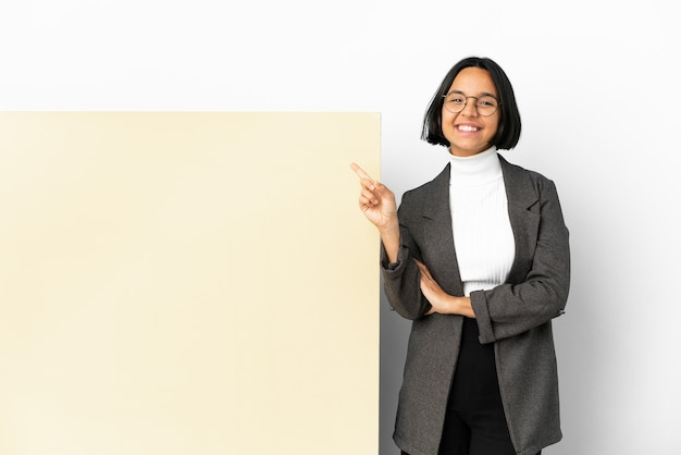 Femme de race mixte jeune entreprise avec une grande bannière sur fond isolé heureux et pointant vers le haut