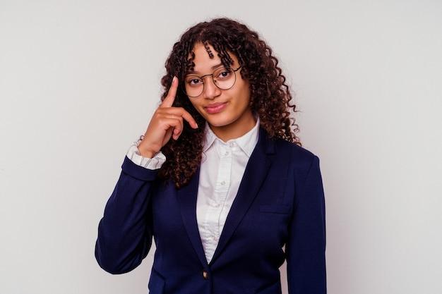 Femme de race mixte jeune entreprise isolée sur fond blanc pointant le temple avec le doigt, pensant, concentré sur une tâche.