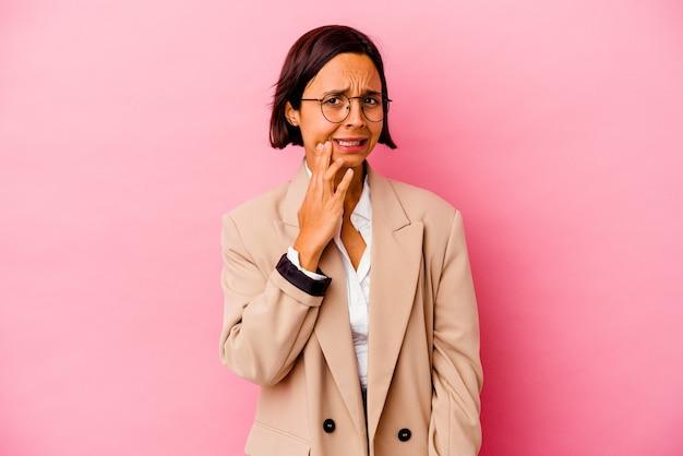 Femme de race mixte jeune entreprise isolée sur fond rose ayant une forte douleur aux dents, douleur molaire.