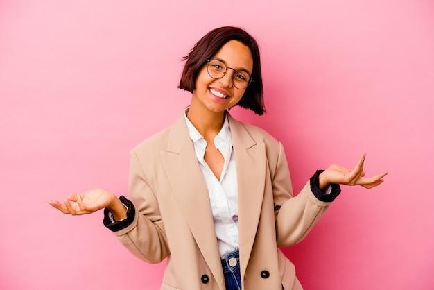 Femme de race mixte jeune entreprise isolée sur fond rose montrant une expression de bienvenue.