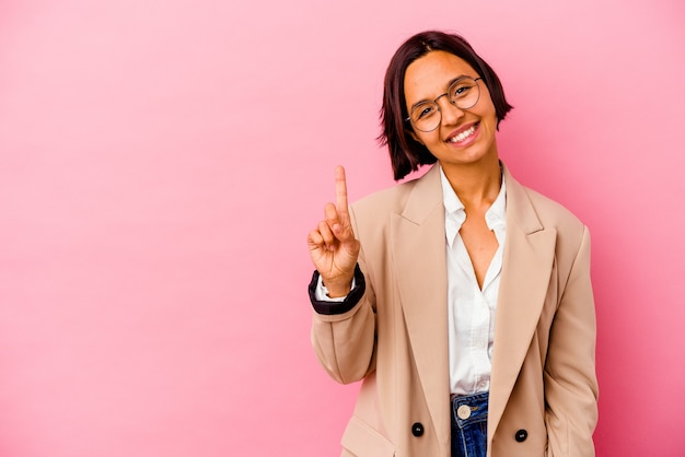 Femme de race mixte jeune entreprise isolée sur fond rose montrant le numéro un avec le doigt.