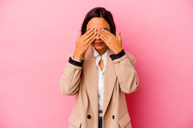 Femme de race mixte jeune entreprise isolée sur fond rose peur couvrant les yeux avec les mains.