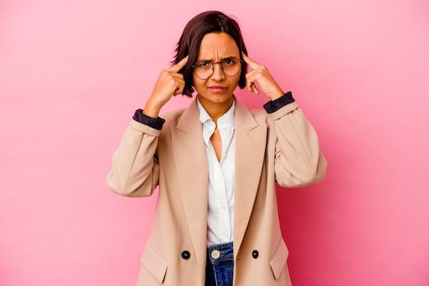 Femme de race mixte jeune entreprise isolée sur un mur rose axé sur une tâche, gardant l'index pointant la tête.