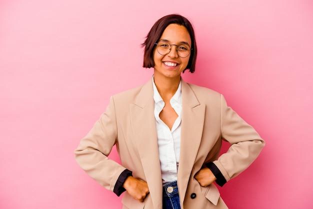 Femme de race mixte jeune entreprise isolée sur mur rose confiant en gardant les mains sur les hanches.