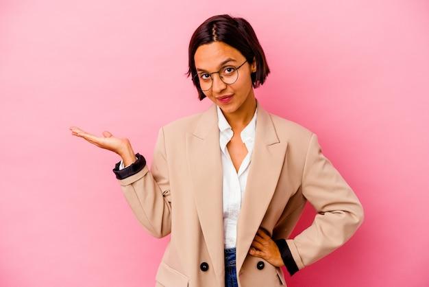 Femme de race mixte jeune entreprise isolée sur un mur rose en doutant et en haussant les épaules dans un geste de questionnement.