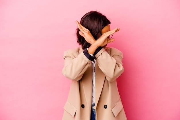 Femme de race mixte jeune entreprise isolée sur mur rose en gardant deux bras croisés, concept de déni.