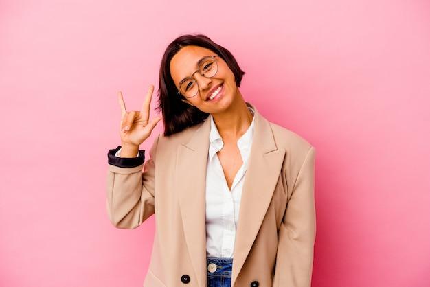 Femme de race mixte jeune entreprise isolée sur un mur rose montrant un geste de cornes comme un concept de révolution.