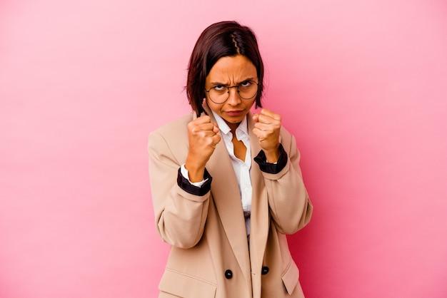 Femme de race mixte jeune entreprise isolée sur mur rose montrant le poing à la caméra, expression faciale agressive.