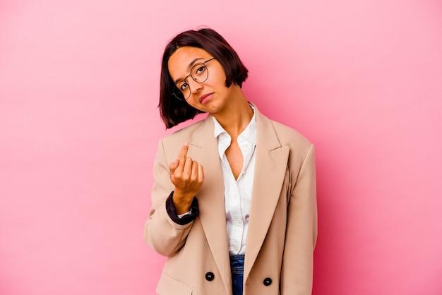 Femme de race mixte jeune entreprise isolée sur mur rose pointant avec le doigt sur vous comme si vous invitiez à vous rapprocher.
