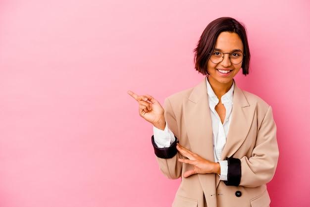 Femme de race mixte jeune entreprise isolée sur mur rose souriant joyeusement pointant avec l'index loin.