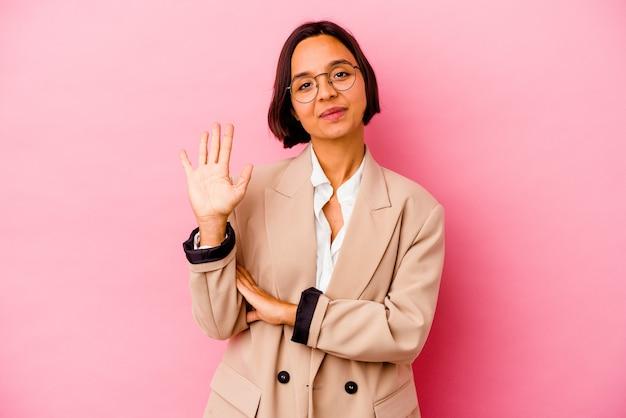 Femme de race mixte jeune entreprise isolée sur mur rose souriant joyeux montrant le numéro cinq avec les doigts.
